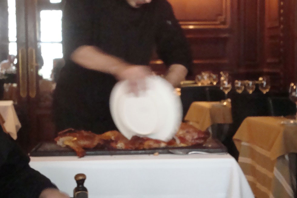 A man chopping up a pig with a plate. Club del Progresso